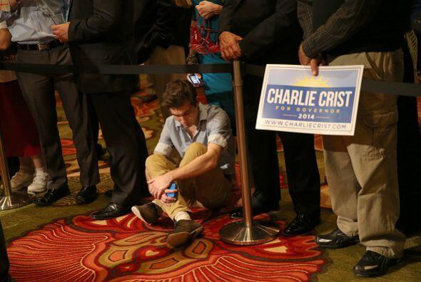 En tanto, los partidarios de su rival Charlie Crist escuchan tristes los...