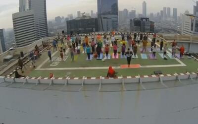 Práctica grupal de yoga frente al sol saliente en Yakarta