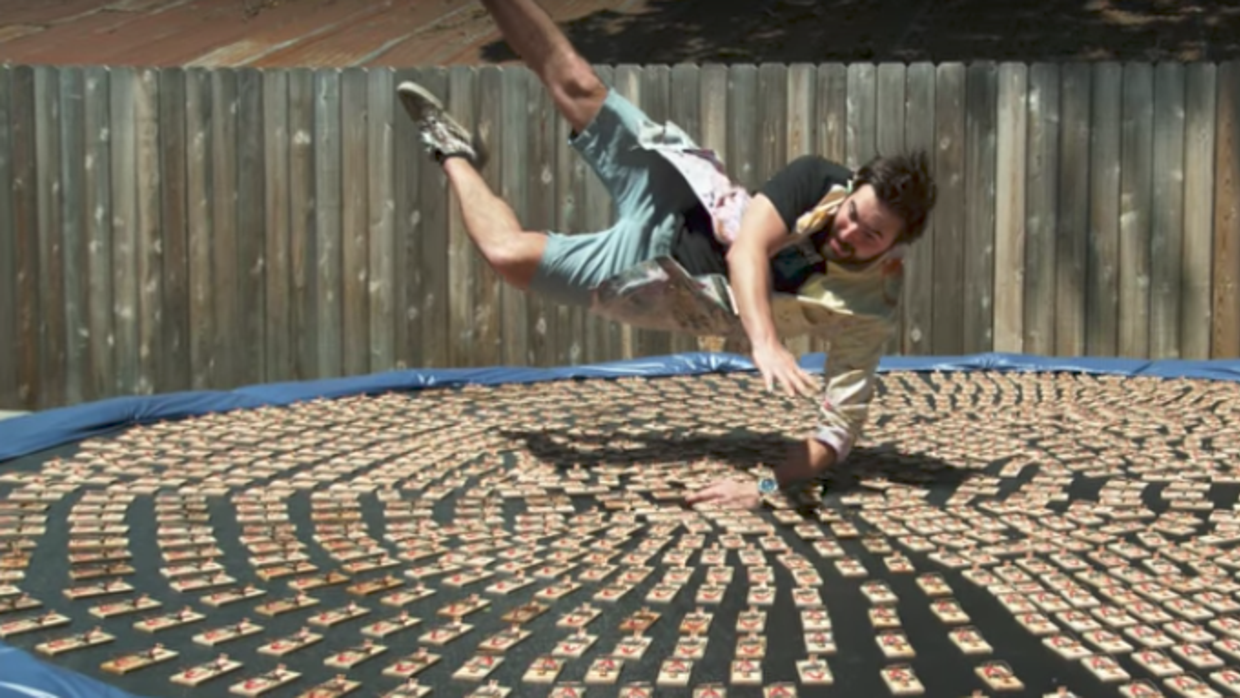 Guy jumps into a trampoline full of mousetraps