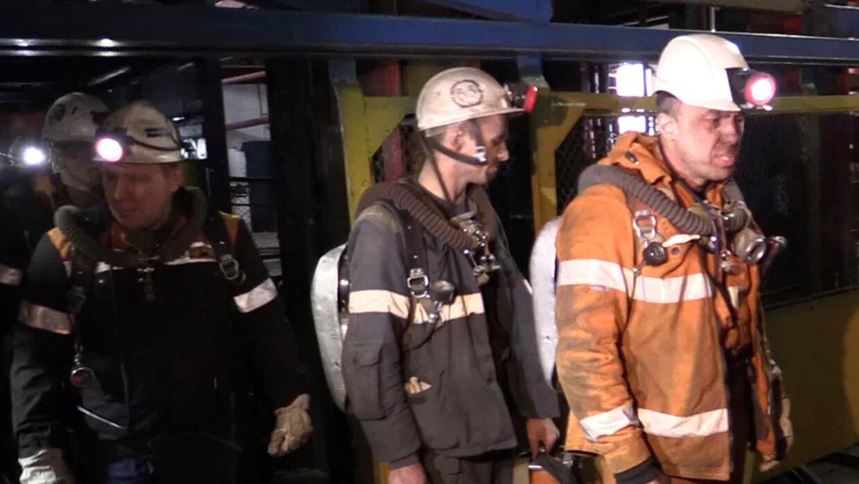 Miembros de equipos de rescate salen de un ascensor