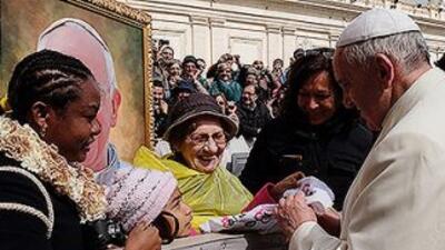 La niña Jersey Vargas le entrega un pañuelo al Papa Francisco que bordó...