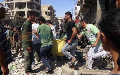 Varias personas cargan una víctima después del atentado con dos bombas e...