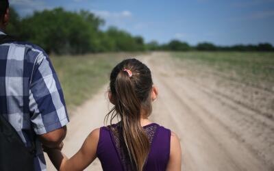 Una niña migrante centroamericana junto a su padre se dirigen rumbo a la...
