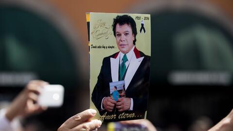 Unos admiradores de Juan Gabriel muestran su foto en México.