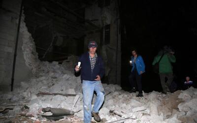 Varias personas caminan sobre escombros en la localidad de Visso, que se...