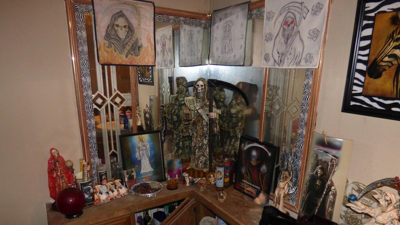 El altar tine diversas figuras y hasta fotos de algunos menores de edad,...