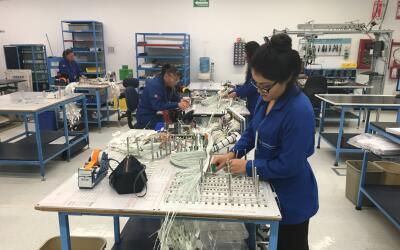 Trabajadores mexicanos realizan labores en una compañía de...