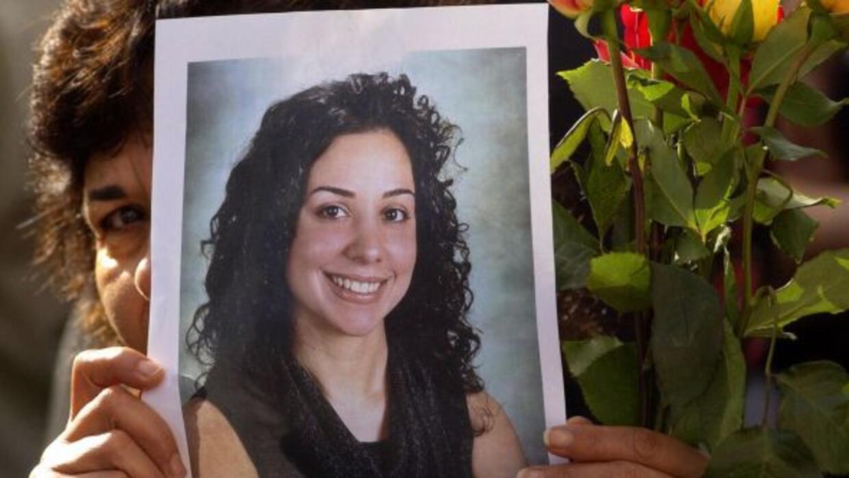 Una mujer sostiene la foto de su hija, quien murió en los ataques del 9/...