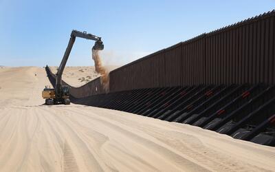 Una excavadora remueve amontonamientos de arena en el muro a la altura d...