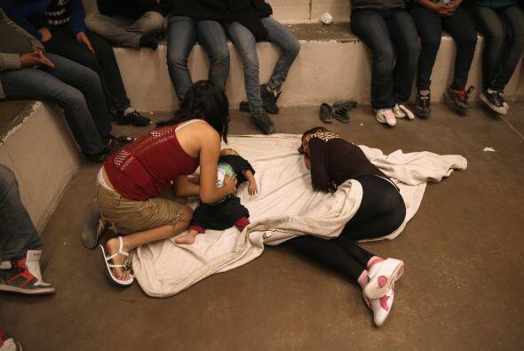 En esta imagen vemos a varios inmigrantes, incluido un bebé, retenidos e...