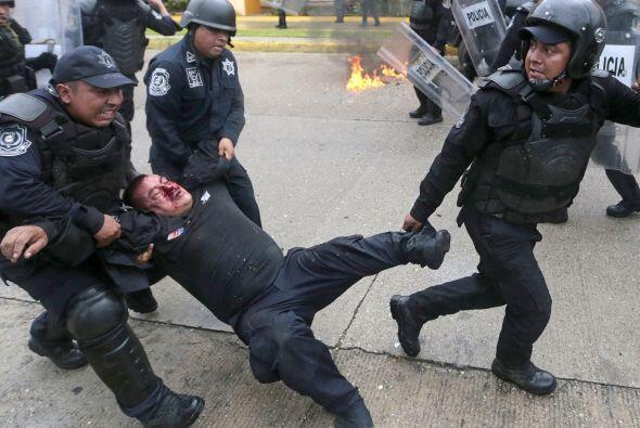 Uno de los policías heridos fue llevado por sus compañeros a una ambulan...