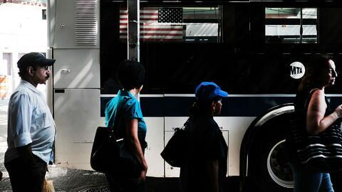Residentes de Queens, en Nueva York, esperan el bus en su paradero.