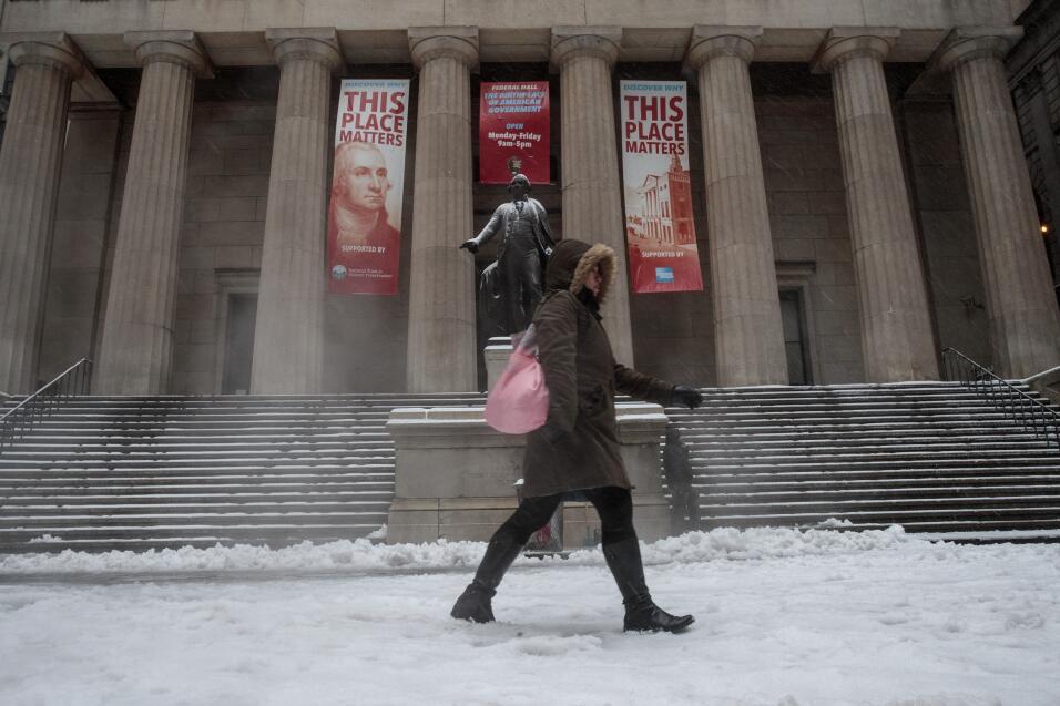 Una mujer se abre paso entre la nieve y la lluvia al caminar frente a Fe...