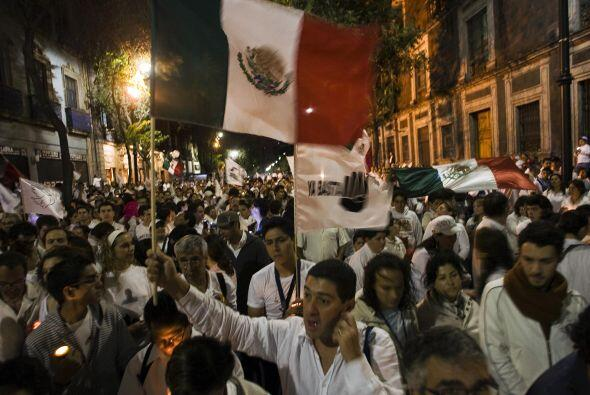Mexicanos sostienen banderas y pancartas mientras marchan durante una de...