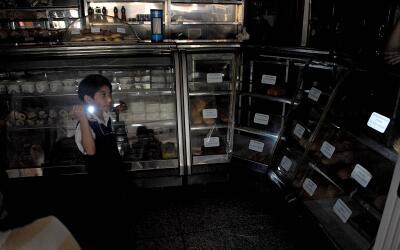 Un niño usa una linterna para iluminar una panadería en San Cristóbal. E...