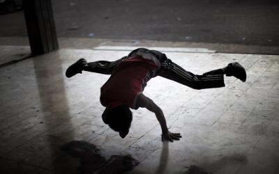 A Libyan breakdancer practices outside a run-down government building in...