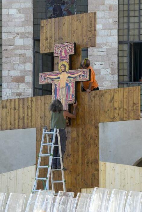Trabajadores preparan el altar frente a la basílica de Asís, en la víspe...