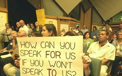 Asistente a la asamblea en la que faltó Rubio porta un cartel que...
