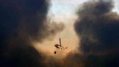 Un helicóptero lanza agua para extinguir uno de los focos del incendio....