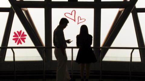 A couple looks out towards Malaysia's skyline