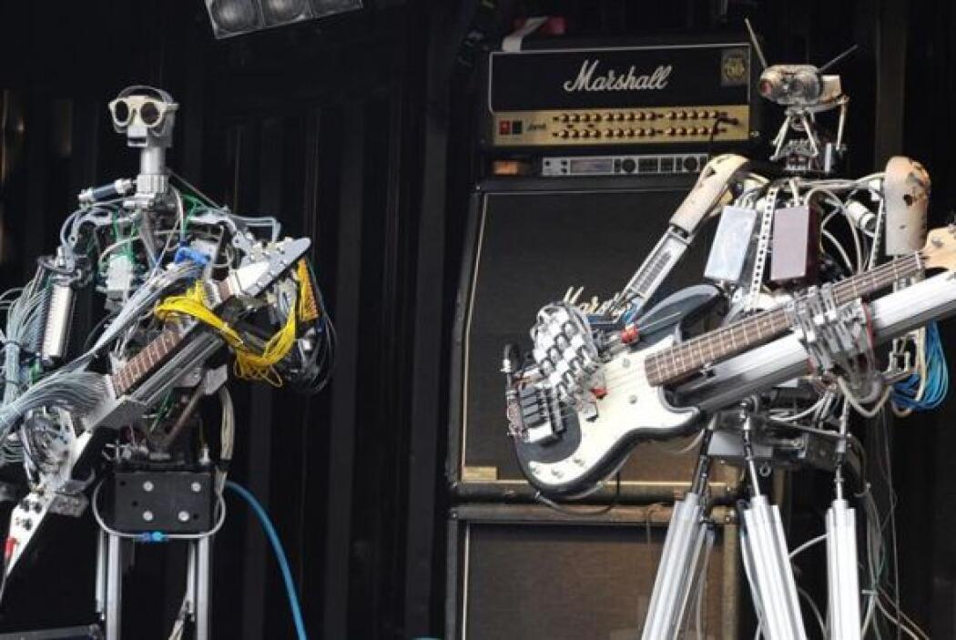 Dos robots tocan instrumentos durante el concierto de la banda de robots...