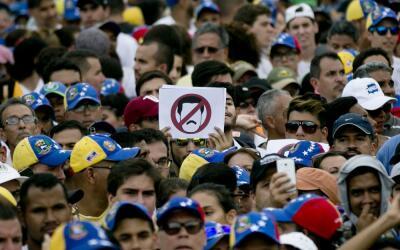 Manifestantes en Caracas con un cartel contra el presidente Nicol&aacute...