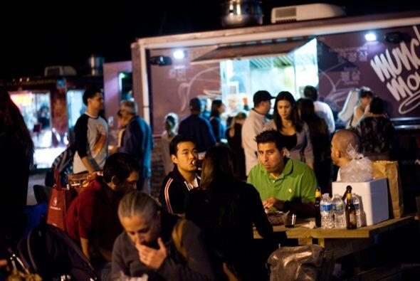 Familias y amigos comparten comidas de diferentes camiones en una misma...