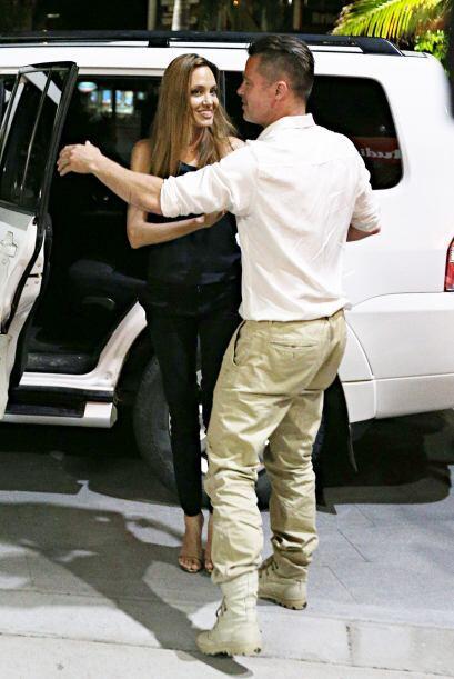 Brad, muy caballeroso, ayudó a Angelina a bajar del auto.  Mira a...
