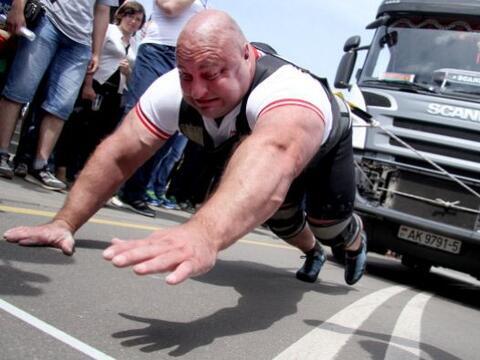 Un atleta tira de un camión de 15 toneladas en un evento de camiones de...