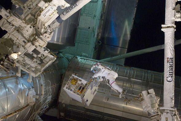 Con los pies asegurados en un brazo robótico de la EEI, el astron...