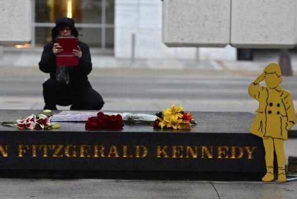 Una mujer toma una fotografía del memorial del expresidente estad...