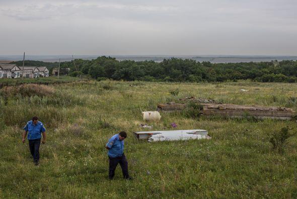 Habitantes de la zona caminan entre escombros esparcidos a lo largo de v...