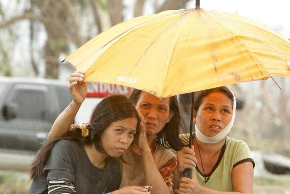 Mujeres víctimas del supertifón Haiyan aguardan ayuda en la ciudad de Ta...