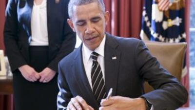 Presidente Barack Obama, en la oficina oval, firma una orden ejecutiva d...