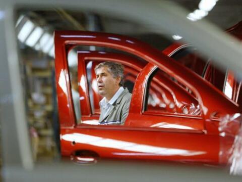Un trabajador mira a las puertas del nuevo coche Dacia Logan en la f&aac...