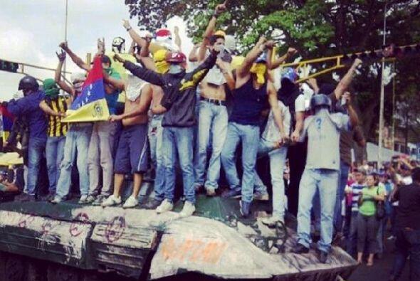 Decenas de manifestantes rodearon y se subieron sobre una tanqueta de la...