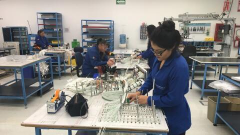 Trabajadores mexicanos realizan labores en una compañía de ensamblaje