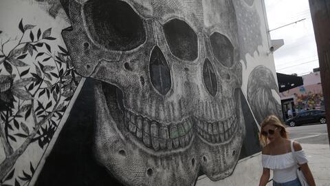 Una joven camina por delante de un grafitti con una calavera en Wynwood,...