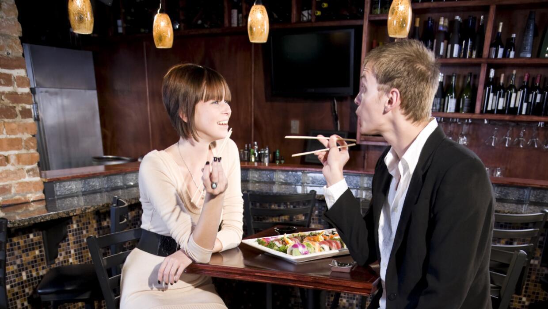 Pareja en bar comiendo sushi