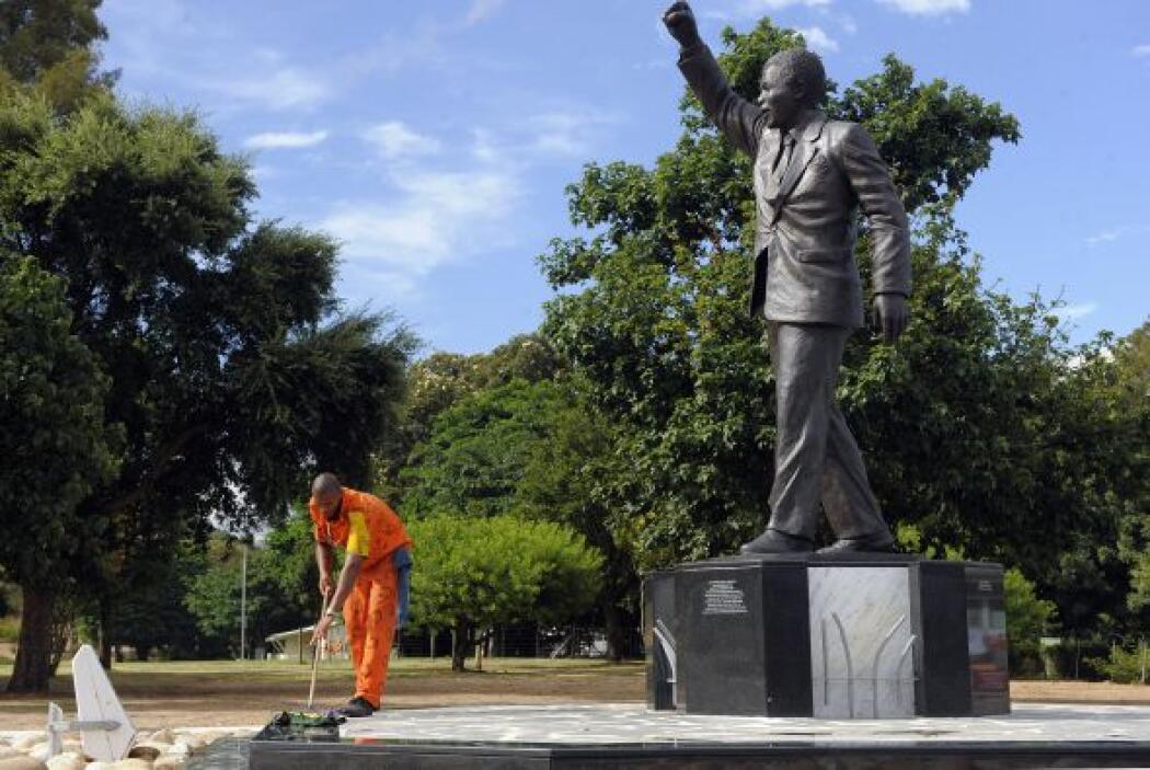 Un recluso limpia la base de una estatua de bronce que representa el ex...