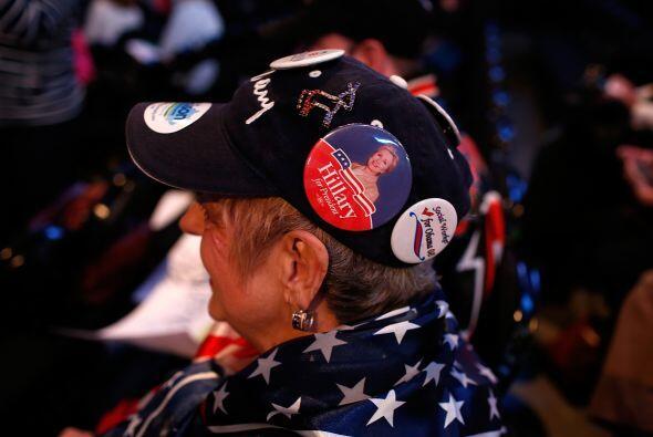 En tanto, también en Kentucky esta votante lleva en su gorra botones en...