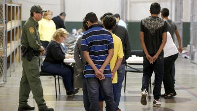 Un grupo de niños migrantes es procesado en un centro de detenci&...