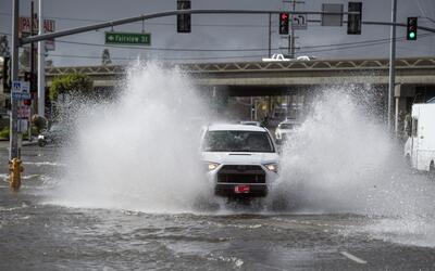 Un vehículo cruza por una calle inundada en el condado de Orange...