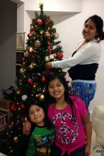 La Familia Morales Santillan mientras adornan su arbolito.