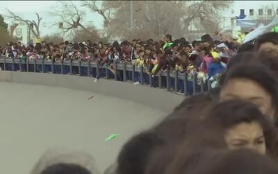 Unidos de la mano, cientos de inmigrantes forman una valla humana en la...