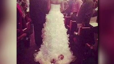 Mujer ata a su bebé a la cola de su vestido de novia