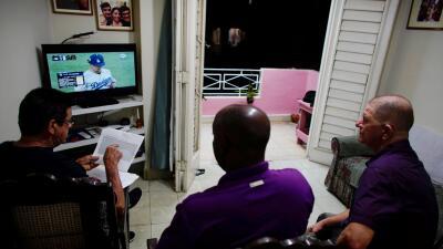 Un grupo de cubanos la retransmisión en diferido que hizo la tele...
