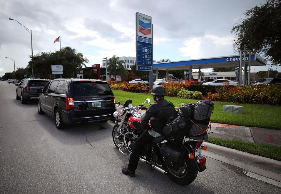 Largas filas en muchas estaciones de gasolina, como en esta de Doral, al...