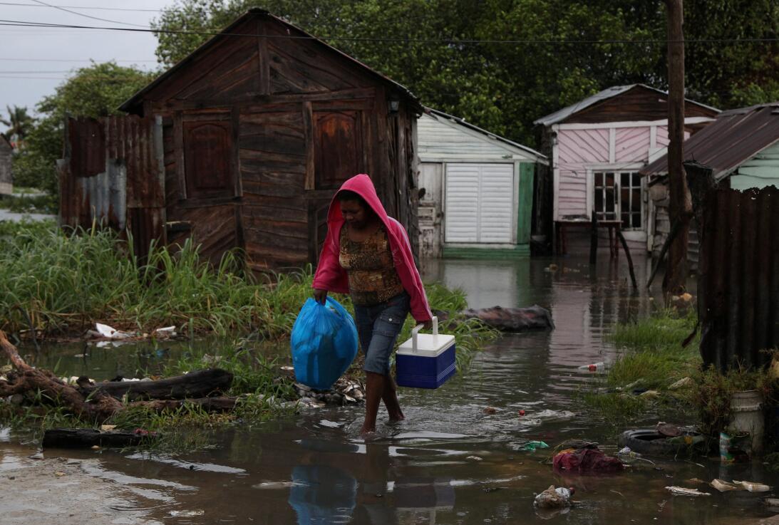 Una mujer camina por los inundados caminos de Nagua, luego de que el hur...