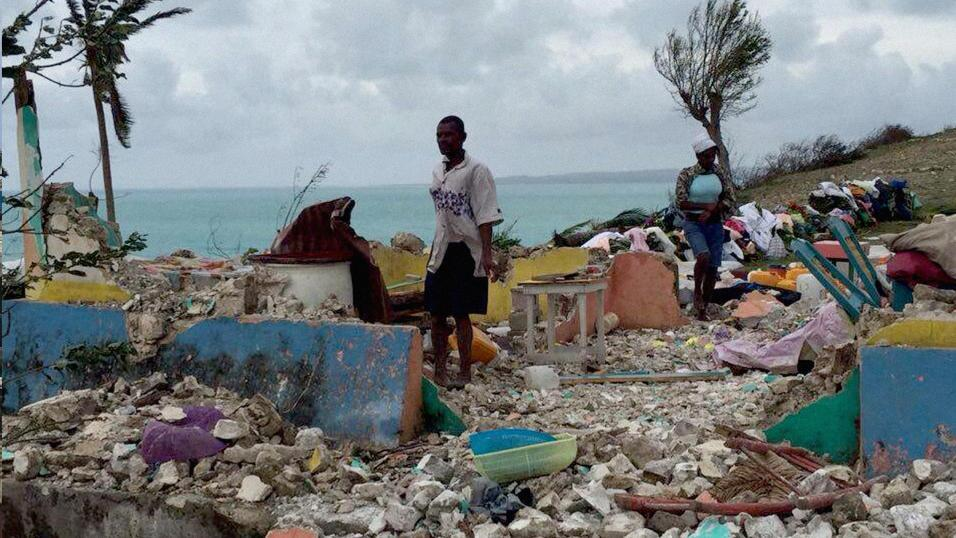 A man and a woman pick through rubble of a home in Ile-a-Vache after the...